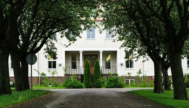 En allé leder fram till entrén till stort vitt hus.