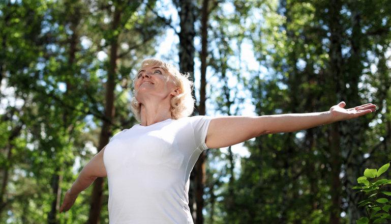 Leende kvinna står i skogen med utsträckta armar och blicken uppåt..