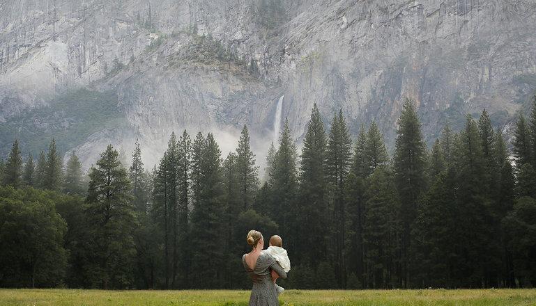 Kvinna med barn i famnen står vänd från betraktaren och ser ut över en äng som följs av granskog framför en hög bergvägg.