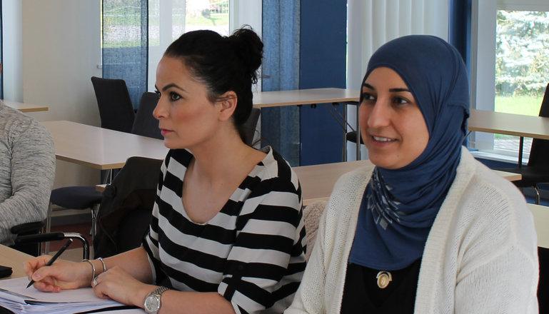 Två tjejer sitter i ett klassrum.