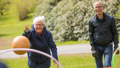 Två aktiva pensionärer som kastar en boll.