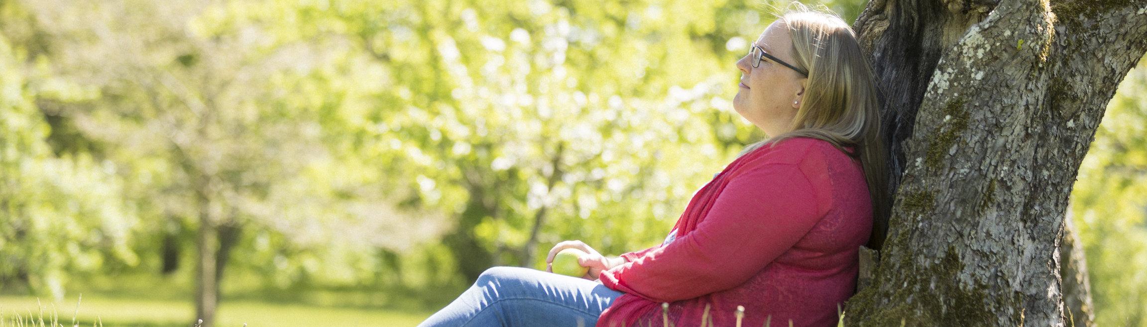 Tjej sitter på marken i en park och lutar sig mot en trädstam.