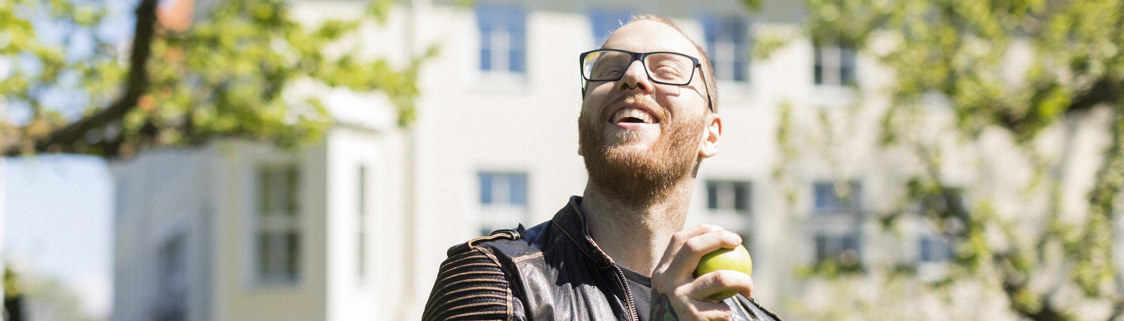 Kille i park med äpple i handen.