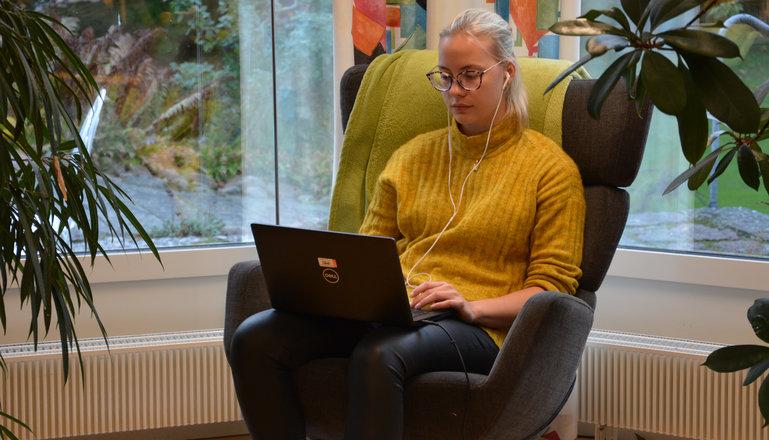 En tjej som sitter i en snurrfåtölj och studerar.