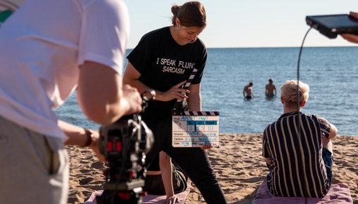 Tre personer som är med vid en filminspelning på en strand.