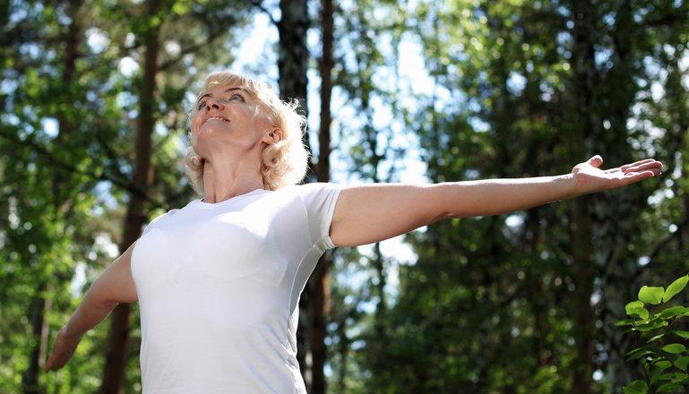 Kvinna med utsträckta armar tittar mot himlen i skogen.