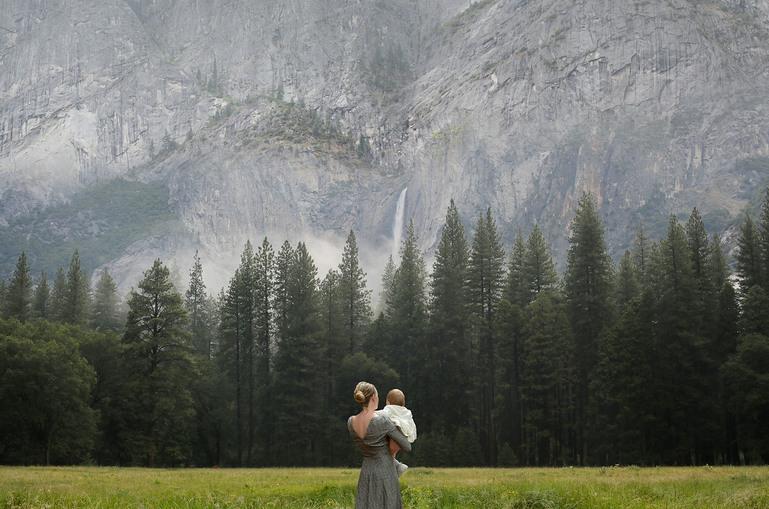 En kvinna bär sitt barn och ser ut över en äng mot en skog framför en bergvägg.