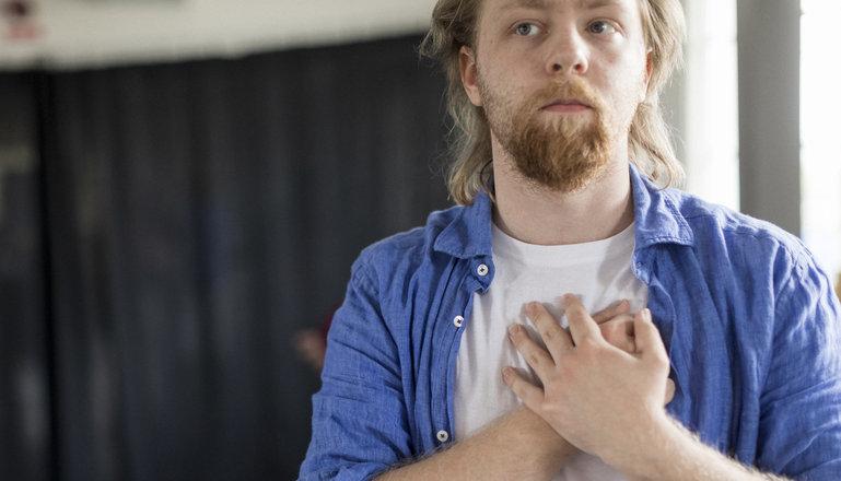 En person håller sina händer över hjärtat.