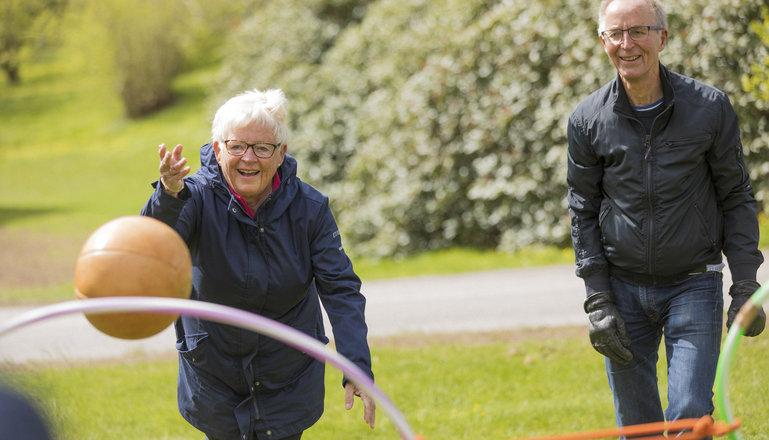 Två seniorer kastar boll i en park.