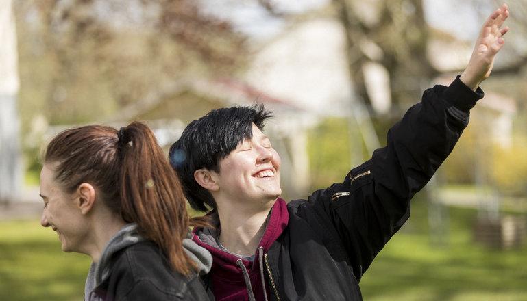 Två leende personer gör rörelser i en park.