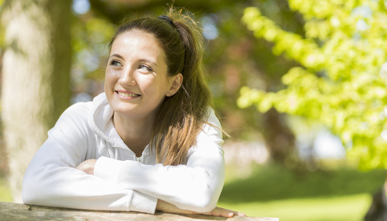 En tjej i en solig och grön park.