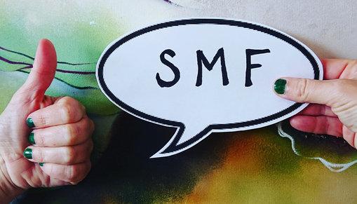 """En tumme upp framför en pratbubbla med texten """"SMF""""."""