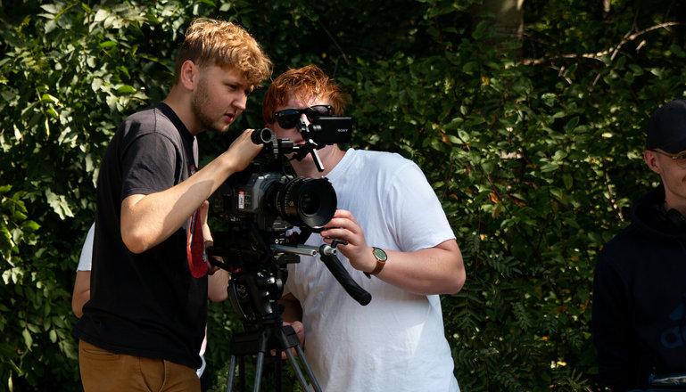 Två killar studerar en filmkamera.