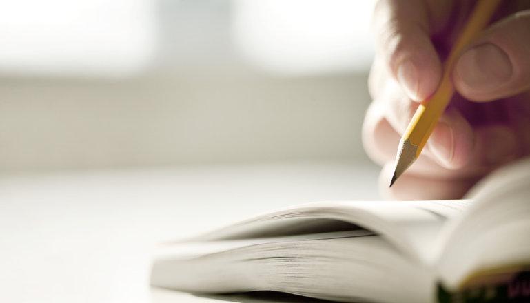En hand som håller i en penna och skriver anteckningar.