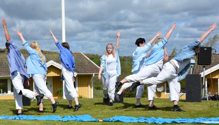 Sju personer står i en dansposition.