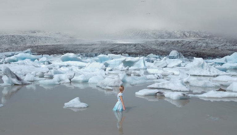 Flicka som står i vatten omgiven av isflak.
