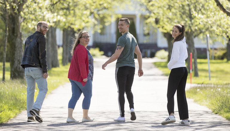 Fyra personer går i en allé framför skolhus.