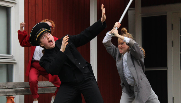 En scen från en teateruppsättning. En polis och två skurkar.