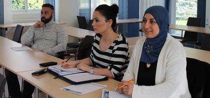 Två kvinnor och en man sitter i ett klassrum