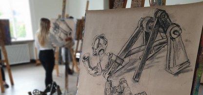 En teckning på maskindelar som sitter på ett staffli. I bakgrunden ser man en flicka som står och tecknar.
