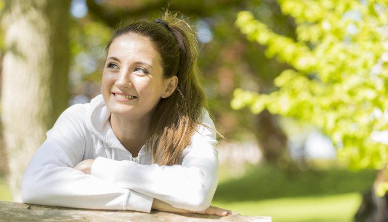 Flicka i vit tröja som sitter och ler i solen.