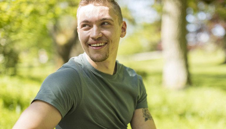 En kille sitter på en parkbänk och ler i solen.