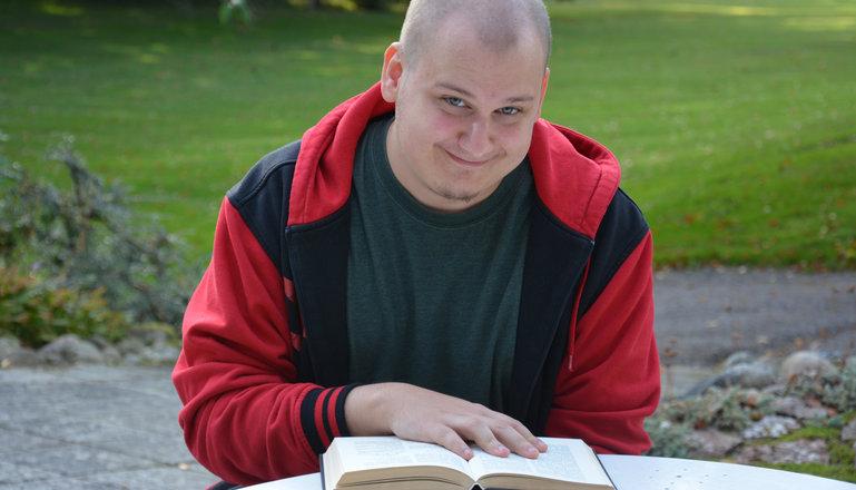 En kille som sitter och läser i en bok.
