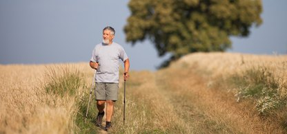 En man som promenerar med stavar på en landsväg.